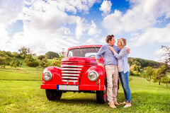 Senior couple hugging, vintage styled red car, sunny nature Royalty Free Stock Photos