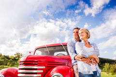 Senior couple hugging, vintage styled red car, sunny nature Stock Photo