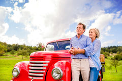 Senior couple hugging, vintage styled red car, sunny nature Royalty Free Stock Image
