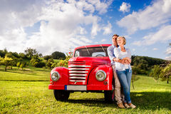 Senior couple hugging, vintage styled red car, sunny nature Stock Images