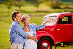 Senior couple hugging, vintage styled red car, sunny nature Stock Photos