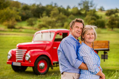Senior couple hugging, vintage styled red car, sunny nature Stock Photography