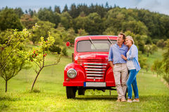 Senior couple hugging, vintage styled red car, sunny nature
