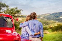 Senior couple hugging, vintage styled red car, sunny nature Stock Image