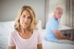 Senior couple ignoring each other on bed in bedroom. At home stock photos