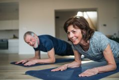 A senior couple indoors at home, doing exercise on the floor. A happy senior couple indoors at home, doing exercise on the floor stock photo