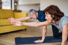 A senior couple indoors at home, doing exercise on the floor. A happy senior couple indoors at home, doing exercise on the floor stock photography