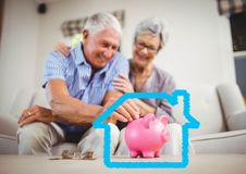 Senior couple insert coins in piggy bank against house outline. Digital composition of senior couple insert coins in piggy bank against house outline stock images