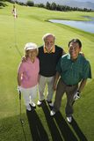 Senior couple with instructor on golf course Royalty Free Stock Photos