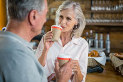 Senior couple interacting with each other while having coffee Royalty Free Stock Images