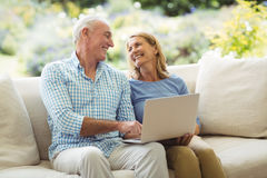 Senior couple interacting with each other while using laptop in living room Stock Images