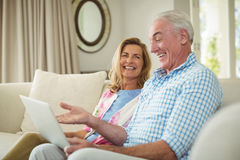 Senior couple interacting with each other while using laptop in living room Royalty Free Stock Photo
