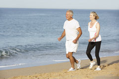 Senior Couple Jogging Along Beach Stock Images