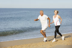 Senior Couple Jogging Along Beach Stock Photos