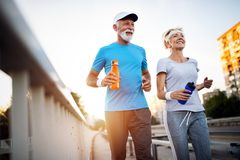 Mature couple jogging and running outdoors in city. Senior couple jogging and running outdoors in nature royalty free stock images