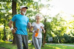 Mature couple jogging and running outdoors in nature stock image