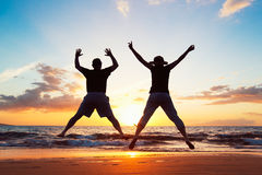 Senior Couple Jumping into the Air. Senior Couple Enjoying Sunset at the Beach royalty free stock images