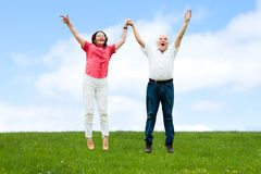 Senior Couple Jumping On Field Royalty Free Stock Image