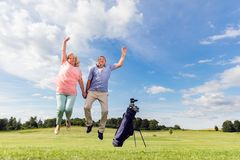 Senior couple jumping on a golf course. royalty free stock images