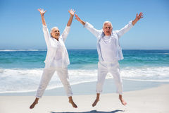 Senior couple jumping with raised arms Stock Photo
