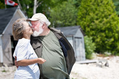 Senior couple kissing. A senior couple on the beach, with boathouses in the background, kissing each other Royalty Free Stock Photos