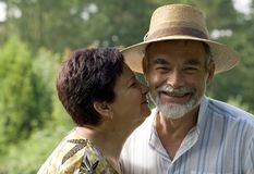 Senior couple kissing. An attractive senior couple kissing outdoors Royalty Free Stock Photography