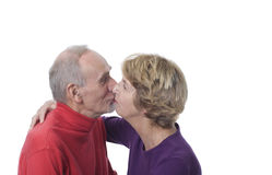 Senior couple kissing. Affectionate happily married couple kissing. White background royalty free stock images