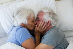 Senior couple kissing each other in bedroom. At home Stock Photos