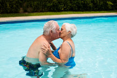 Senior couple kissing each other in the pool. On a sunny day Royalty Free Stock Photo