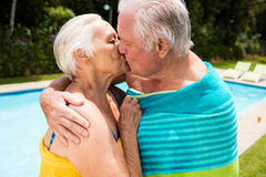 Senior couple kissing each other at poolside. On a sunny day Royalty Free Stock Images