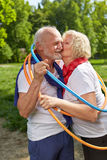 Senior couple kissing in a hoop in nature. Happy senior couple kissing in a hoop in nature in summer Stock Photo