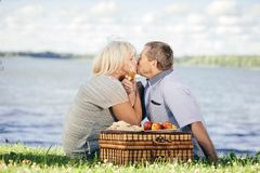 Senior couple kissing by the lake. Picnic. Happy elderly marriage concept Royalty Free Stock Images