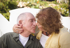 Senior Couple Kissing in the Park Stock Photo