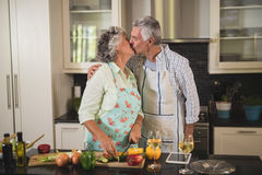 Senior couple kissing while preparing food in kitchen. At home Stock Photography