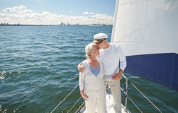 Senior couple kissing on sail boat or yacht in sea. Sailing, age, tourism, travel and people concept - happy senior couple kissing on sail boat or yacht deck Royalty Free Stock Photography