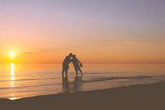 Senior couple kissing at sunset. Senior couple kissing in the water at sunset Royalty Free Stock Images