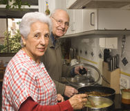 Senior couple at kitchen. Happy senior couple cooking at home Royalty Free Stock Photos