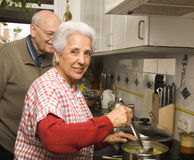 Senior couple at kitchen. Happy senior couple cooking at home Royalty Free Stock Images