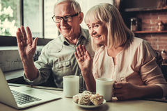 Senior couple in kitchen. Beautiful senior business couple is using a laptop, waving, drinking tea and smiling while connecting with family in kitchen Royalty Free Stock Photo