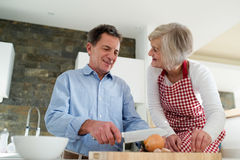 Senior couple in the kitchen cooking together. Stock Photo