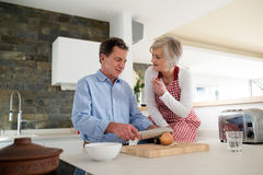 Senior couple in the kitchen cooking together. Stock Photos