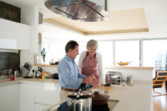 Senior couple in the kitchen cooking together. Royalty Free Stock Photos