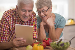 Senior couple at the kitchen. Culinary inspiration taken from the Internet Stock Images