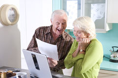 Senior couple in kitchen with laptop computer and paperwork Royalty Free Stock Image
