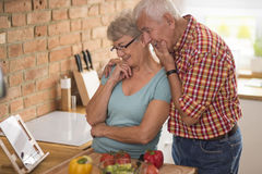Senior couple at the kitchen. Senior couple looking for inspiration on the Internet Stock Image