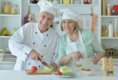 Senior couple at kitchen. Portrait of a senior couple at kitchen cooking Royalty Free Stock Image