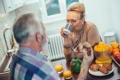 Senior couple in the kitchen preparing breakfast royalty free stock photos