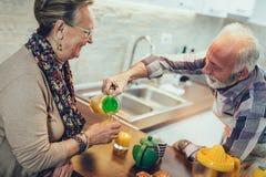 Senior couple in the kitchen preparing breakfast stock image