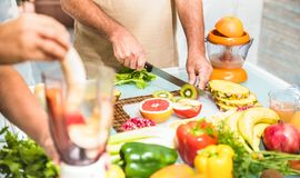 Senior couple in kitchen preparing healthy vegetarian food. Detail of senior couple in kitchen with healthy food - Retired people cooking at home preparing Stock Photo