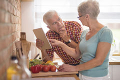 Senior couple at the kitchen. Wife helping husband with soluting the problem Stock Photos
